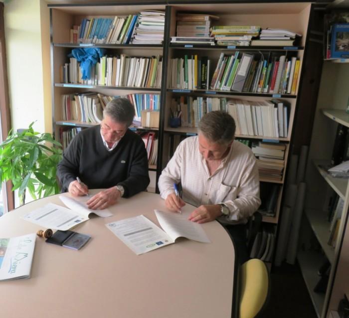 Federico Aja y Carlos Sánchez firmando el acuerdo.