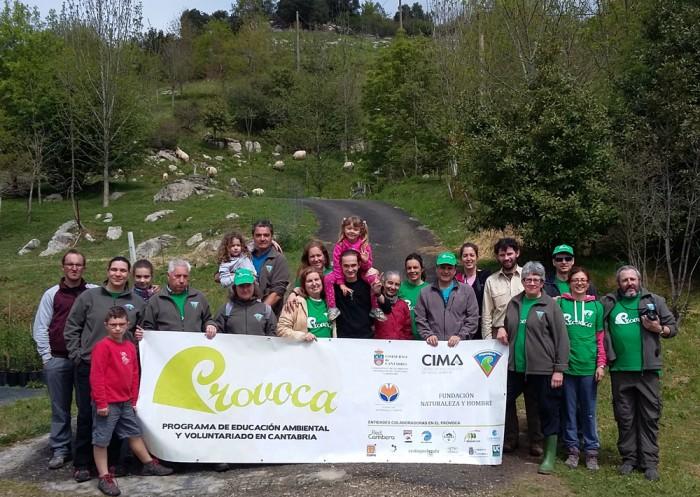 Voluntarios del PROVOCA sostienen la bandera del programa.