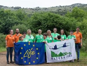 Un grupo de voluntarios que se congregó en los Pozos de Valcaba muestra las banderas del programa LIFE y la Red Natura 2000.